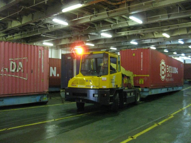 Los estibadores sevillanos estiban los contenedores sobre sus plataformas en la bodega principal del barco.