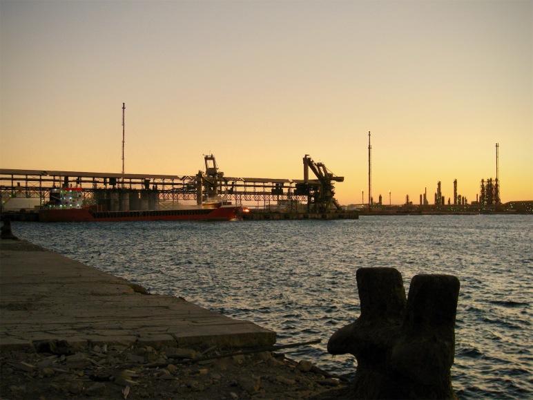 El Mistral carga sus bodegas en el puerto de Marsá el Brega al atardecer.